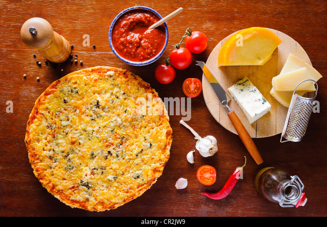 Traditional homemade italian quattro formaggi cheese pizza and ingredients - Stock Image
