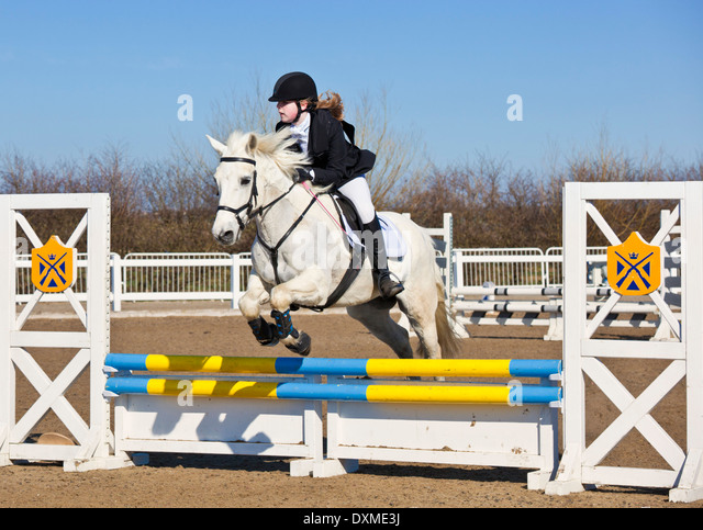 Young girl jumping a white horse pony over a jump at a showjumping event - Stock Image