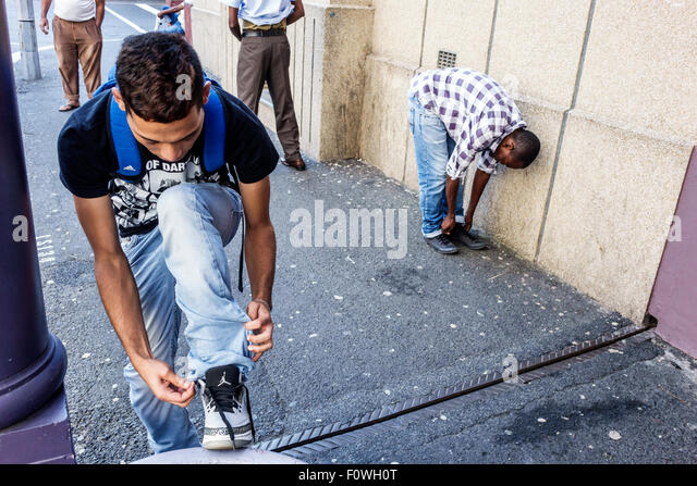 Cape Town South Africa African City Centre center Loop Street teen boy student tying shoe - Stock Image