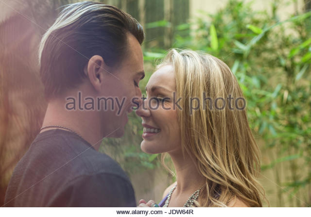 Young romantic couple, face to face, smiling, outdoors - Stock-Bilder