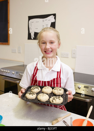 A Girl shows her cooked rolls - Stock Image