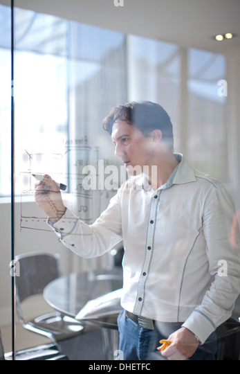 Man drawing architectural plans on glass wall - Stock-Bilder