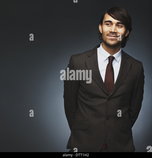 Handsome young man looking away smiling on black background. Male model in business suit looking at copyspace. - Stock Image