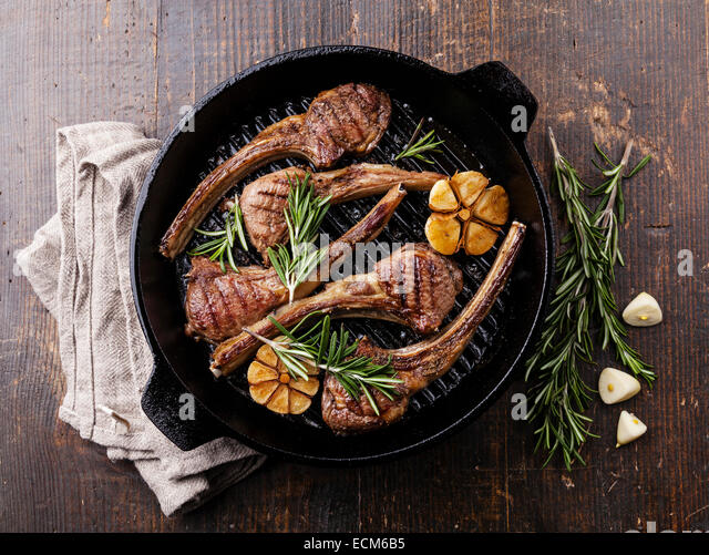 Roasted lamb ribs with rosemary and garlic on grill pan on dark background - Stock Image