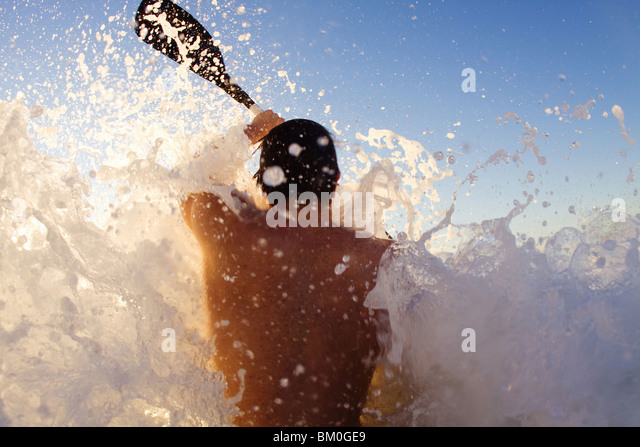 Young man kayaking on high wave, Sun Coast Beach, Durban, KwaZulu-Natal Province, South Africa - Stock Image