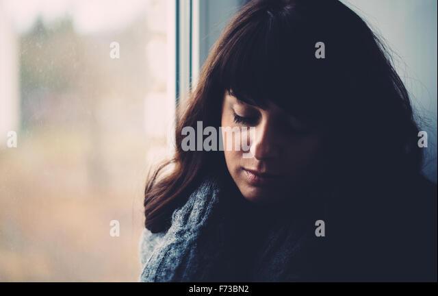 Young woman longs near a window. - Stock Image