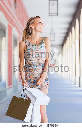 Young woman carrying shopping bags in city shopping mall - Stock Image
