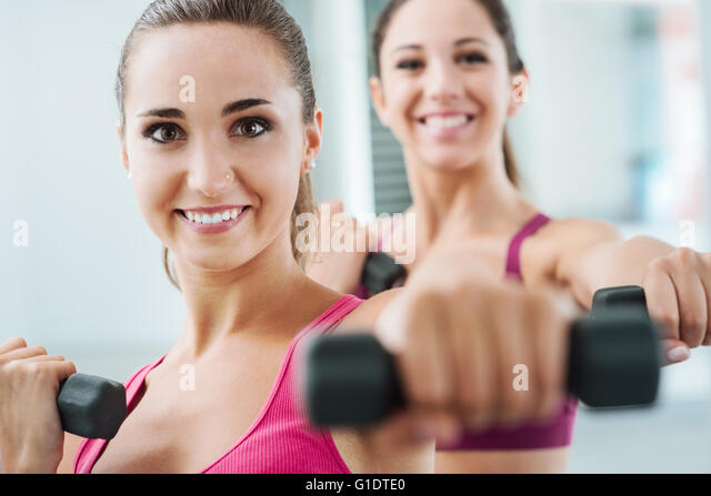 Cheerful young women exercising at the gym and weightlifting using dumbbells, they are smiling at camera - Stock Image