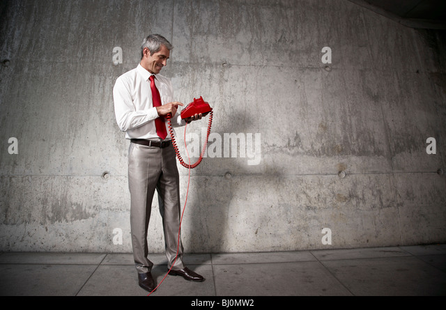businessman dialing red telephone - Stock Image
