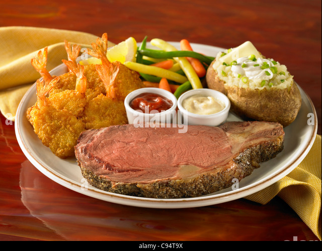 Prime rib and shrimp dinner with loaded stuffed potato and vegetable - Stock Image
