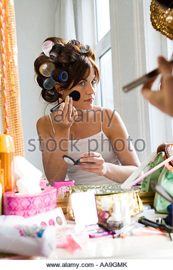 Young woman applying makeup with her hair in curlers - Stock Image