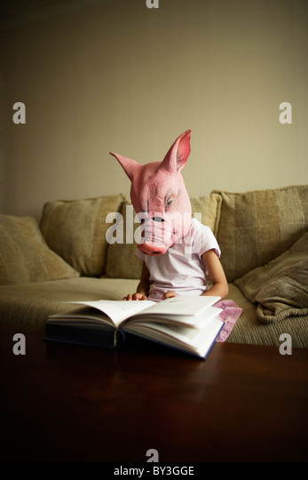 Girl in pig mask reads book - Stock Image