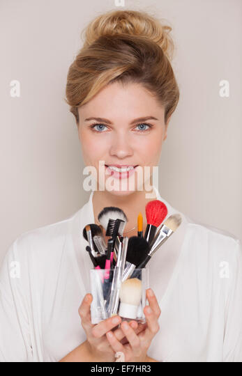 Beautiful woman holding assorted makeup brushes - Stock Image