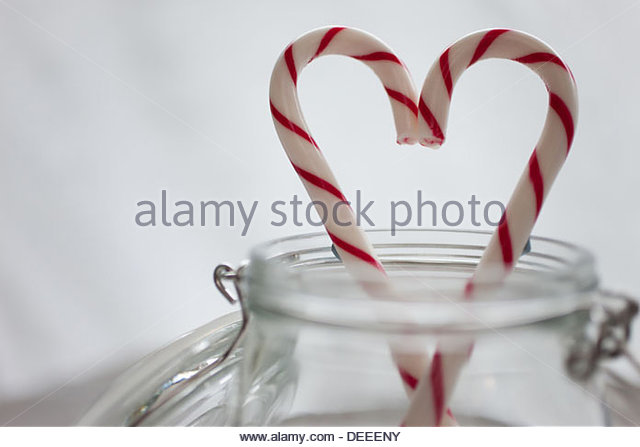 Close up of candy canes forming heart-shape - Stock Image