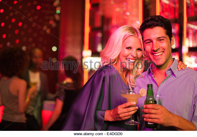 Couple holding drinks in nightclub - Stock Image