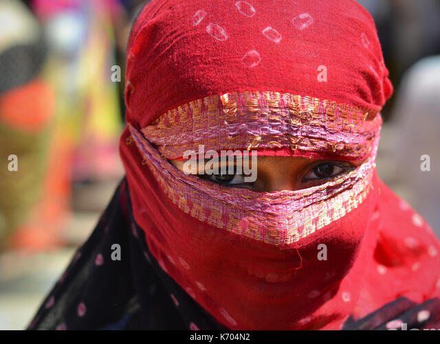 Young Indian woman with smiling eyes, covering her hair and face with a trendy secular, half-sheer red headscarf; - Stock Image