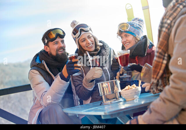 Skier friends drinking and eating at balcony table apres-ski - Stock-Bilder