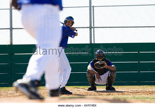 Young men playing baseball, pitcher in foreground, focus on catcher and batter at home plate in background - Stock Image
