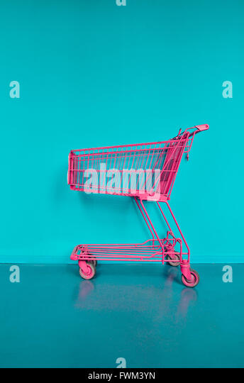 Pink Shopping Cart Against Turquoise Wall - Stock Image