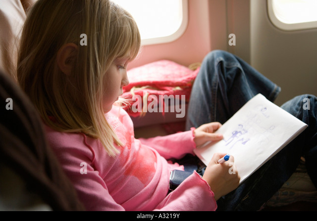 Young girl sitting in an airplane and drawing in a sketch pad - Stock-Bilder