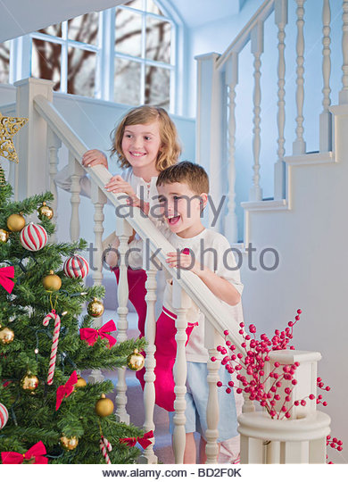 Boy and girl standing on stairs above Christmas tree - Stock Image