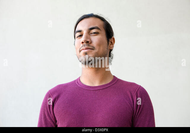 Portrait of young adult long-haired mexican-american male with expression of half-smile, doubt, and playfulness - Stock Image