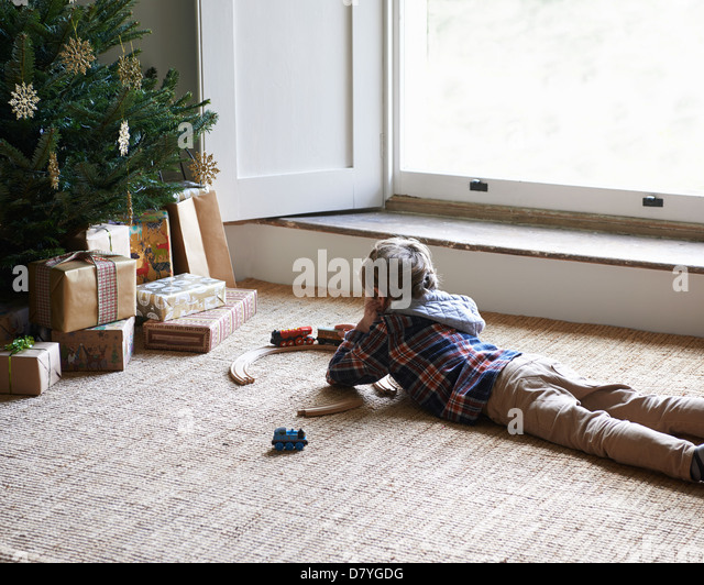 Boy playing with trains by Christmas tree - Stock Image