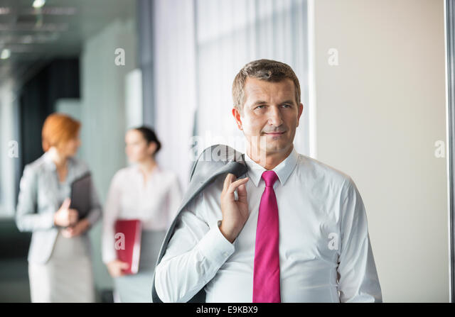 Businessman holding coat over shoulder with female colleagues in background at office - Stock Image