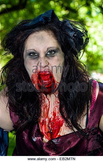 A woman dressed as snarling violent zombie drooling blood. - Stock Image