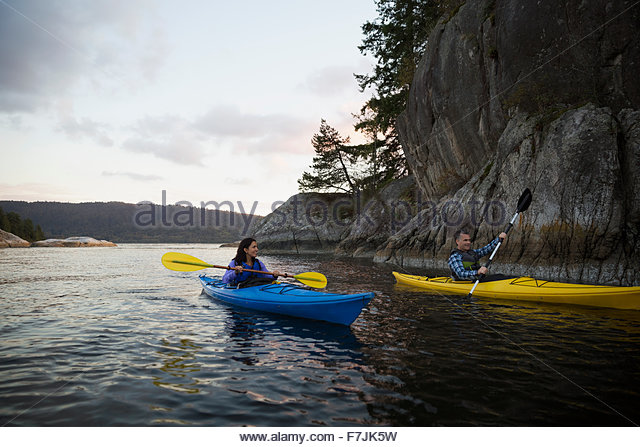 Couple canoeing on lake at sunset - Stock Image