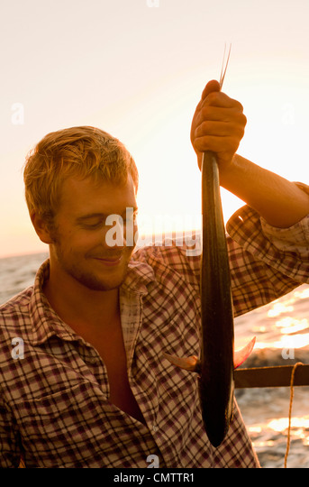 Smiling man while catching fish - Stock Image