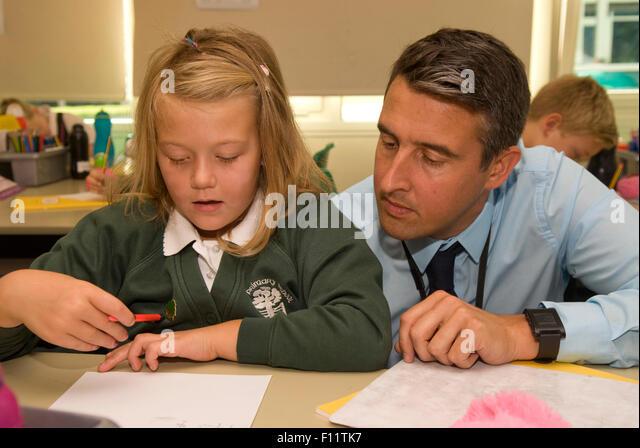 Primary school teacher assisting pupil in classroom, Midlands, UK. - Stock Image