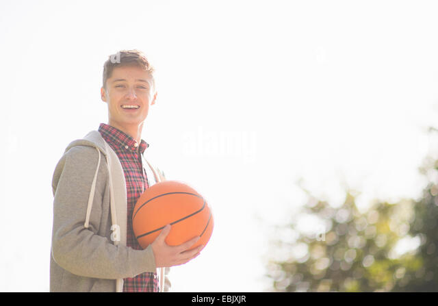 Portrait of smiling young man holding basketball - Stock Image
