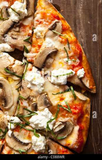 Thin and crispy crust Pizza with Mozzarella, Mushrooms, Goat Cheese and Basil prepared by Gianni Scappin, Chef/Owner - Stock Image