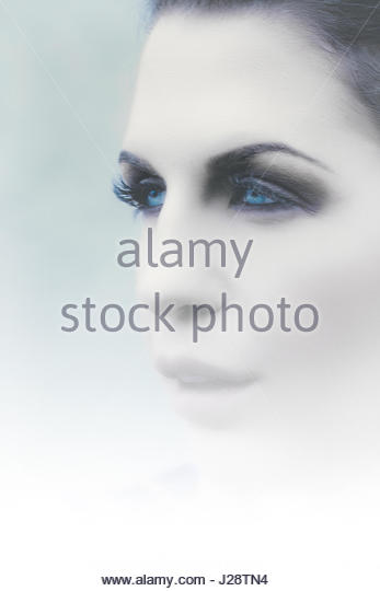 Profile portrait of blue eyed woman in thick fog - Stock Image