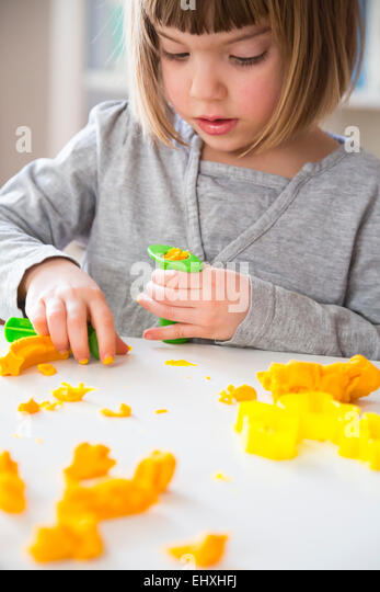 Little girl playing with yellow modeling clay - Stock Image