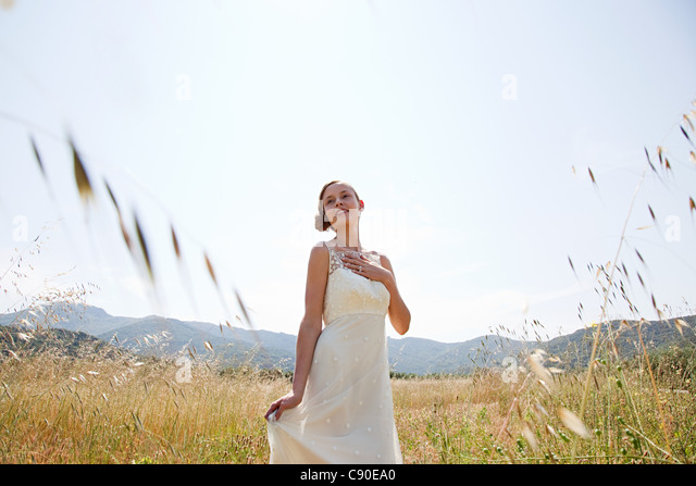Bride wearing wedding dress alone in field - Stock Image