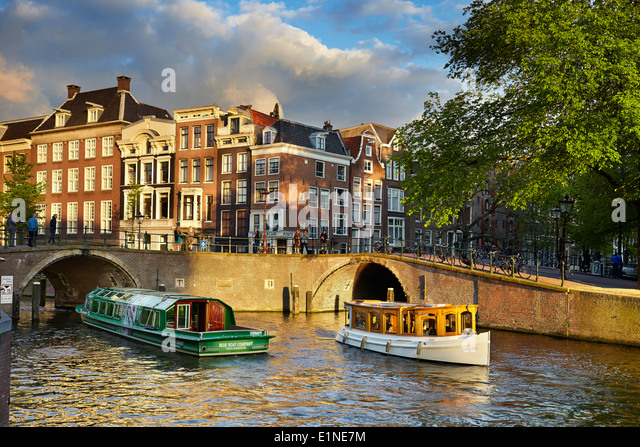 Tourist boat at Amsterdam canal - Holland Netherlands - Stock Image