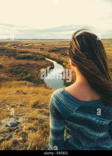 Canada, Saskatchewan, Val Marie, Rear view of woman overlooking prairie and river vista in fall - Stock Image