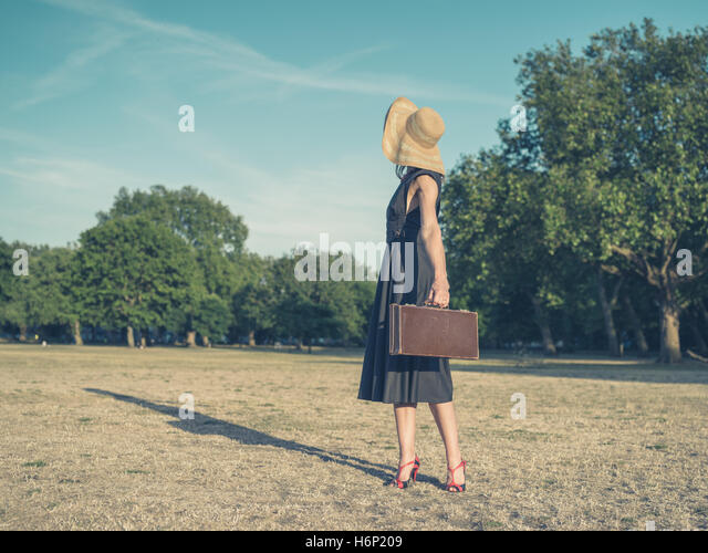 Vintage filtered shot of an elegant young woman wearing a dress and a hat standing in the park with a briefcase - Stock Image