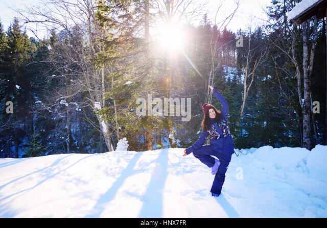 Woman in winter clothes practicing tree yoga pose in snow by forest, Austria - Stock Image