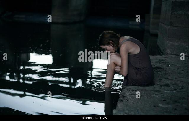Pensive Caucasian woman sitting at edge of water - Stock Image