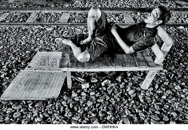 A man sleeping beside a railway track, in the Yan Nawa district of Bangkok, Thailand, South East Asia. - Stock Image