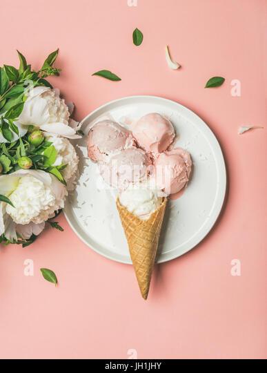 Strawberry and coconut ice cream, cones, white peonies, top view - Stock Image