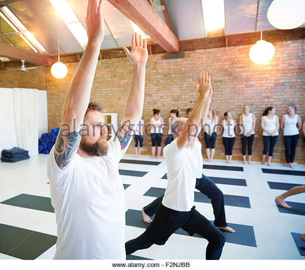Women watching men in yoga class - Stock Image