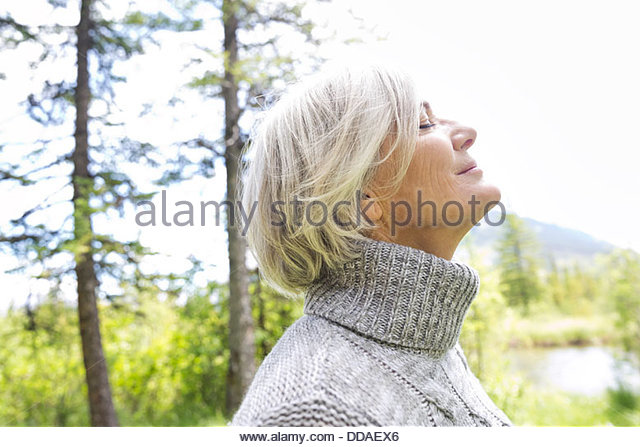 Close-up of woman in forest with eyes closed - Stock Image