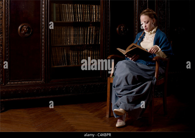 Retro style dressed women reading a book - Stock Image