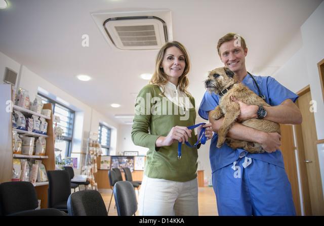 Veterinarian holding dog in lobby - Stock Image