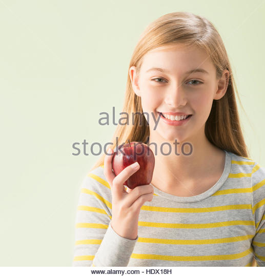 Caucasian girl holding red apple - Stock Image