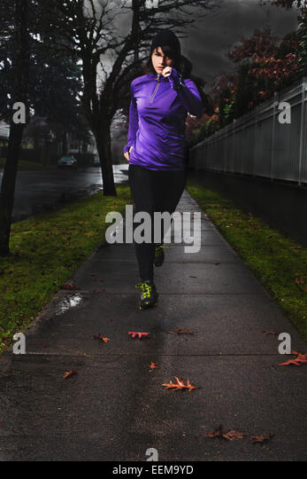 Young woman running along city sidewalk after rain - Stock Image